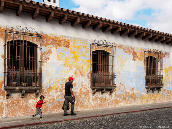 Guatemalan father and son walking in front of texture wall